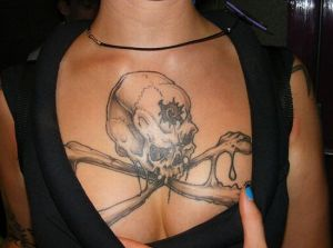 Large skull and crossbones chest tattoo on girl.